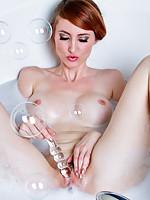 Sizzling redhead takes a masturbation break to test her glass dildo in the bathtub